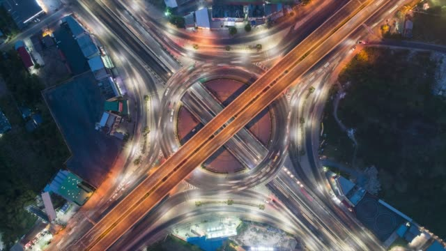 4k dusk to night time lapse : aerial top view highway road roundabout or intersection, circle at night for transportation, distribution or futuristic background. - roundabout stock videos & royalty-free footage