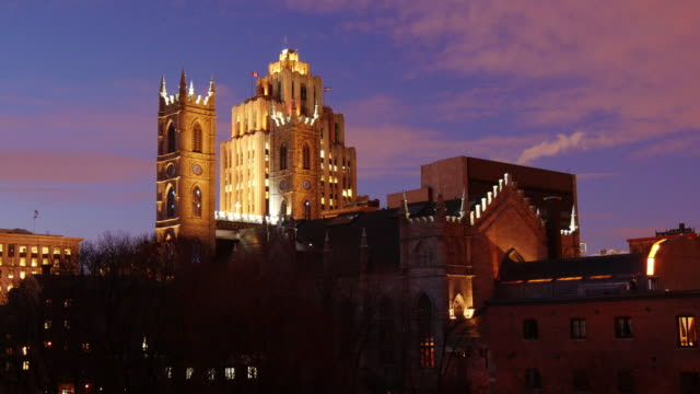 dusk to night time lapse montreal with notre dame in front of aldred building - vieux montréal stock-videos und b-roll-filmmaterial