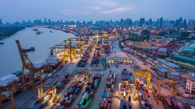4k夕暮れから夜間経過またはハイパーラプス:ターミナル商業港のコンテナ貨物船と業務物流用の作業用クレーン橋積載コンテナ、輸入輸出、出荷または輸送 - タグボート点の映像素材/bロール