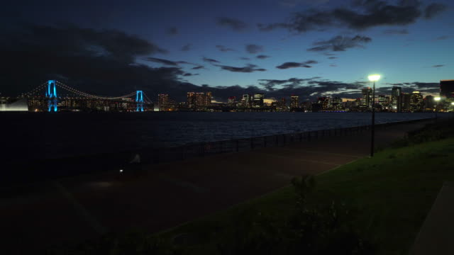 dusk view of rainbow bridge, illuminated by blue / cycling - tokyo bay stock videos & royalty-free footage