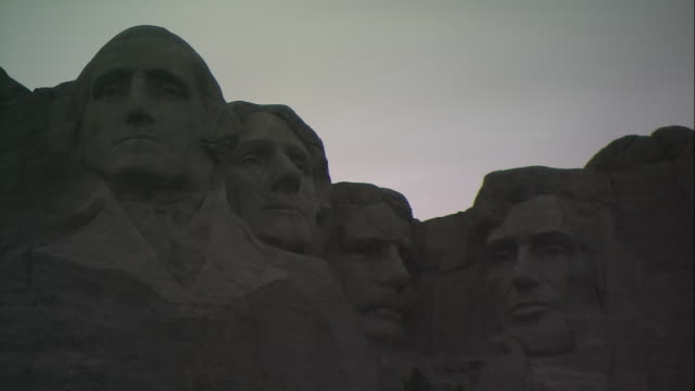 a dusky sky silhouettes the mt. rushmore monument in south dakota. - mt rushmore national monument stock videos and b-roll footage