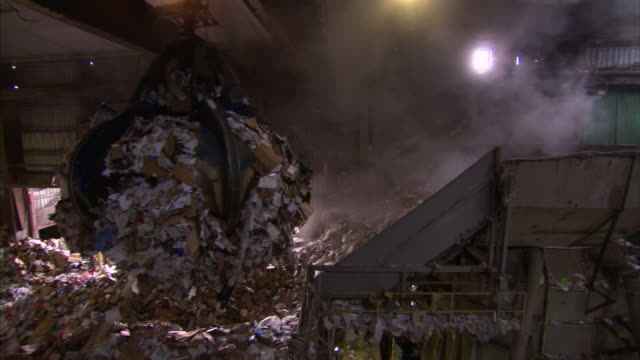 Dust billows as a claw crane moves heaps of paper at a paper collection facility.