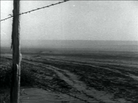 B/W 1936 dust blowing over dusty plain in storm / barbed wire fence in foreground / Dust Bowl