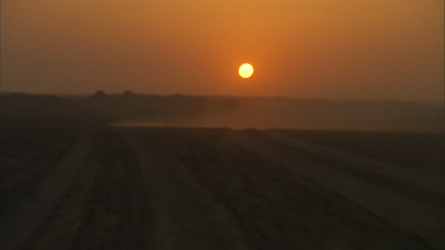 a dust cloud spreads across a desert at sunset. - dust stock videos & royalty-free footage