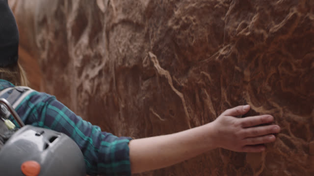 SLO MO. Dust falls as young woman runs hand along rough sandstone walls of slot canyon on Moab hiking trip.