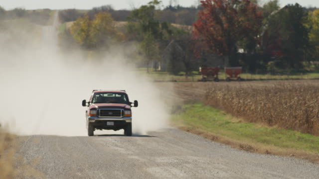dust fills the air as a a pickup truck races toward camera on a rural gravel road. - pickup bildbanksvideor och videomaterial från bakom kulisserna