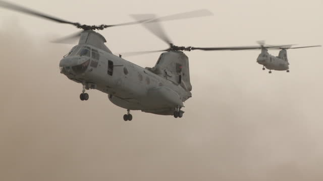 stockvideo's en b-roll-footage met dust flies as two u.s. marine ch-46 transport helicopters land in a field. - afghanistan