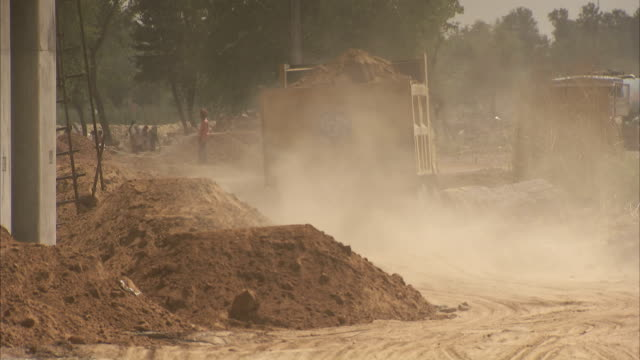 dust flies from a dump truck at a construction site in india. available in hd - baustelle stock-videos und b-roll-filmmaterial