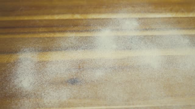 dust flour on wooden working bench for making shortbread
