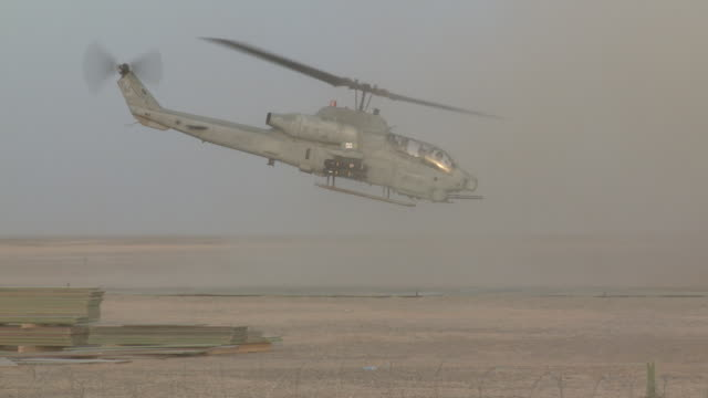 dust rises as a u.s. marine super cobra helicopter takes off from a desert base. - afghanistan stock videos & royalty-free footage