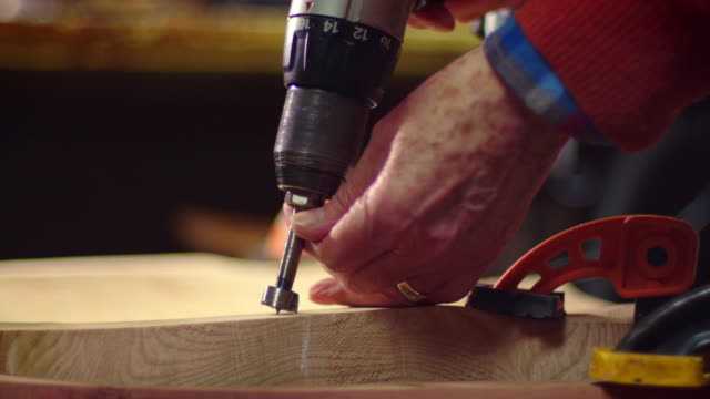 dust rises from wood being drilled into with an electric drill. - accuracy stock videos & royalty-free footage
