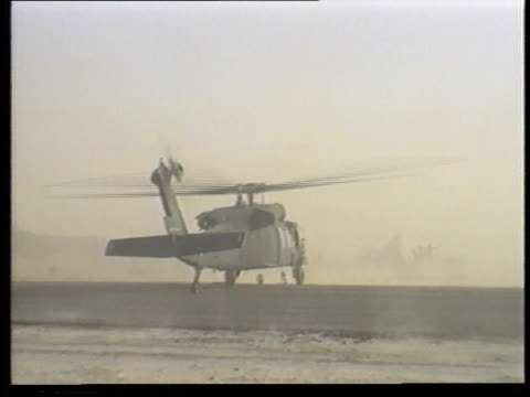 dust swirls as a uh-60 blackhawk lifts off from a desert base. - military helicopter stock videos & royalty-free footage