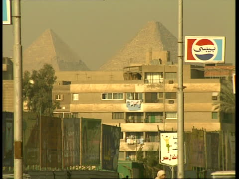 ms dusty city street with traffic passing through frame, pyramids just visible through smog in background, egypt - cairo stock videos & royalty-free footage