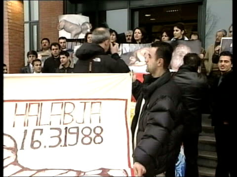 vídeos de stock, filmes e b-roll de dutch businessman found guilty of war crimes the hague kurdish victims and relatives of iraqi chemical attacks in 1980's stand outside court holding... - curdo