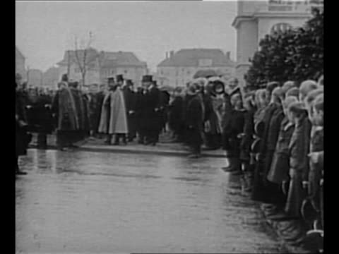 dutch citizens, including young boys at right, line both sides of walkway, raise arms and hats as exiled wilhelm ii approaches with retinue / wilhelm... - esilio video stock e b–roll