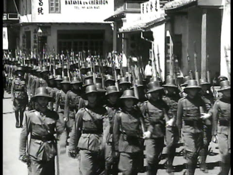 dutch east indies soldiers marching on batavia street. shipyard, ship in dry dock w/ male in silhouette working fg. blast furnace spewing molten... - malaysian ethnicity stock videos & royalty-free footage