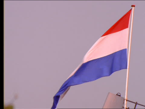 Dutch flag blowing in wind / zoom out to flag on windmill