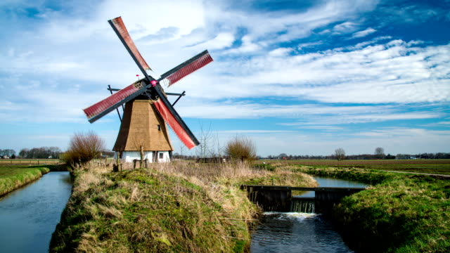 dutch landscape with turning windmill - windmill stock videos & royalty-free footage