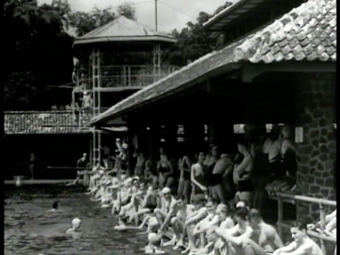 dutch people by swimming pool. people playing in pool. people seated standing by pool talking congregating. dutch colonization. - reportage点の映像素材/bロール