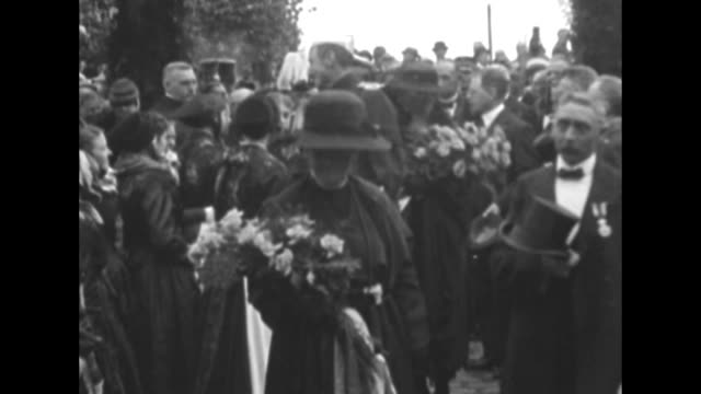 stockvideo's en b-roll-footage met dutch queen wilhelmina holding a bouquet of flowers walks with danish king christian x toward and past camera, officers and another woman follow /... - 1920