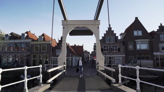 dutch woman walking in empty lockdown streets - pandemic - dutch culture stock videos & royalty-free footage
