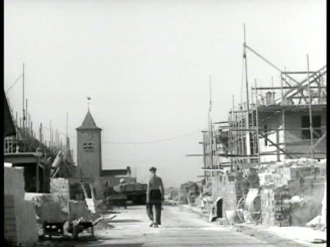 dutch worker walking houses under construction ms topless men laying brick ms workers laying brick rotterdam post world war ii - れんが造りの家点の映像素材/bロール