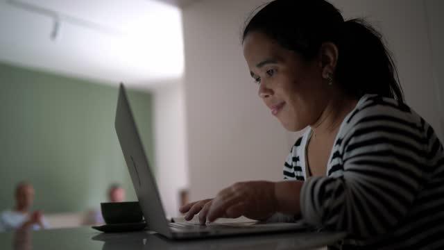vídeos y material grabado en eventos de stock de enanismo mujer usando portátil en casa - una mujer de mediana edad solamente