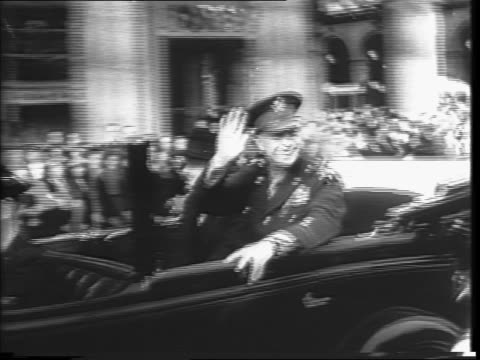Dwight D Eisenhower in car through Paris streets / past French crowds cheering on ramps / back shot of Eisenhower standing in car waving to French...