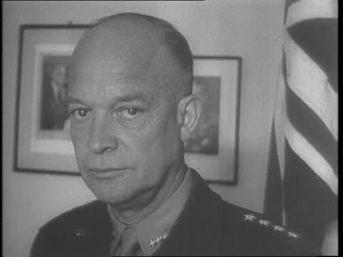 dwight d eisenhower stands before flags / assault boats and troops are landing / landing craft are lined up / soldiers walk on beach / soldiers load... - 1943 stock-videos und b-roll-filmmaterial