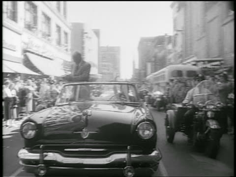 dwight d eisenhower stands waves in convertible in ticker tape parade in city / newsreel - anno 1952 video stock e b–roll
