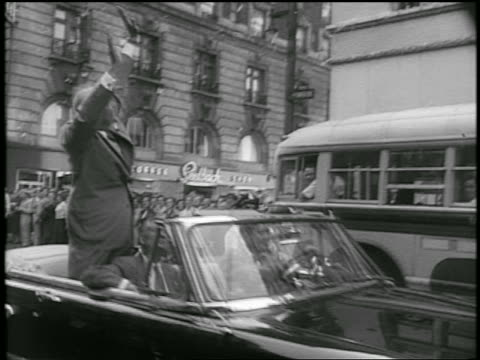 dwight d eisenhower stands waves in moving convertible in parade in city / newsreel - anno 1952 video stock e b–roll