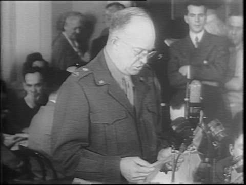 Dwight Eisenhower enters a packed Senate committee hearing room / at a table Eisenhower testifies before the committee / Eisenhower indicates...