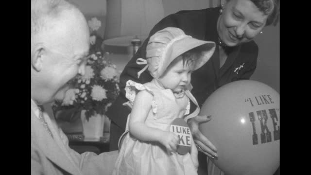 dwight eisenhower holds a baby girl on his lap as mamie eisenhower holding an i like ike balloon stands nearby they coo over the baby who wears an... - television show stock videos & royalty-free footage