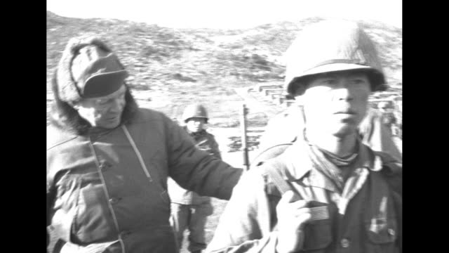 dwight eisenhower in hat and heavy coat stands in back of republic of korea soldier standing at attention and examines what soldier is carrying on... - corea del sud video stock e b–roll