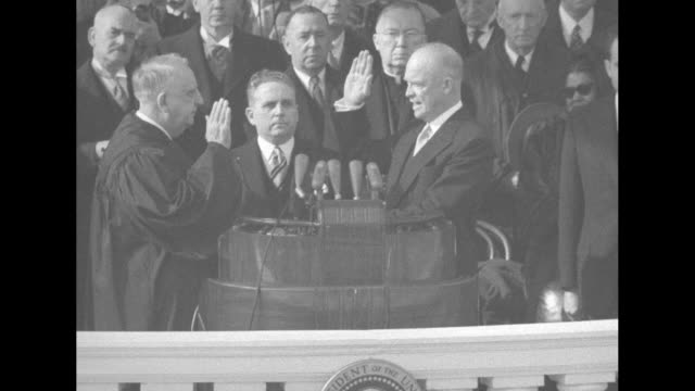 Dwight Eisenhower standing at podium on East Portico of US Capitol takes oath of office with his right hand raised and left hand on a Bible Chief...