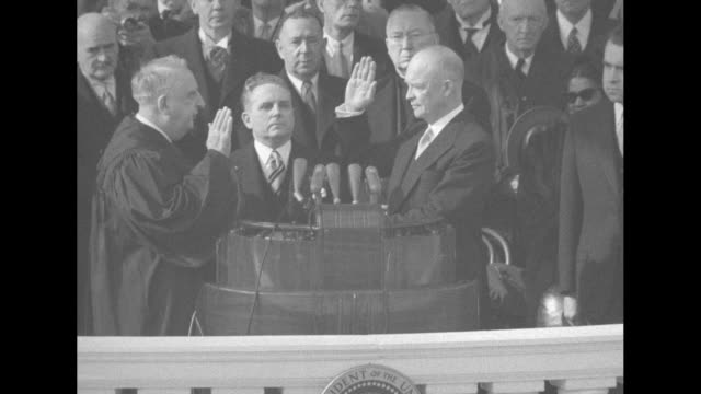 vídeos de stock, filmes e b-roll de dwight eisenhower standing at podium on east portico of us capitol takes oath of office with his right hand raised and left hand on a bible chief... - tomada de posse