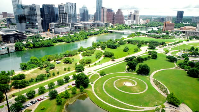 dyanmic pan up to downtown citscape over pond in modern public park - austin , texas , usa - austin texas video stock e b–roll