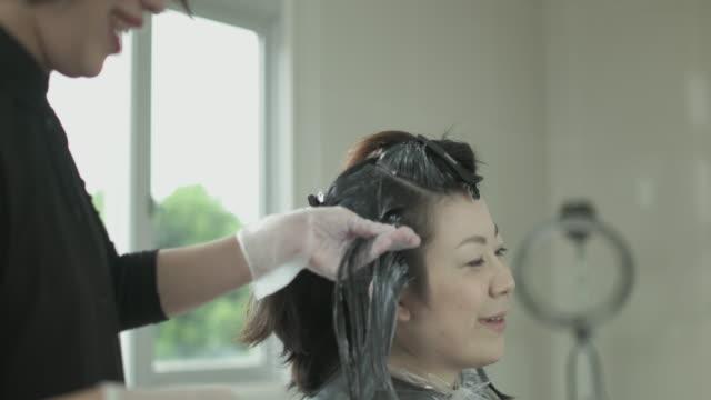 vídeos de stock, filmes e b-roll de dyed hair at beauty salon. japan - cor de cabelo