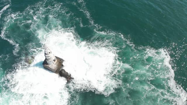 stockvideo's en b-roll-footage met dynamic 4k aerial drone shot of  lighthouse in the sea - vuurtoren