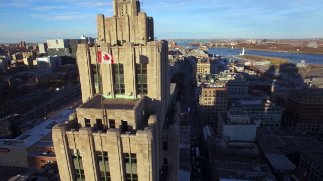 dynamic aerial view of building in downtown montreal to reveal city scape - bandiera del canada video stock e b–roll