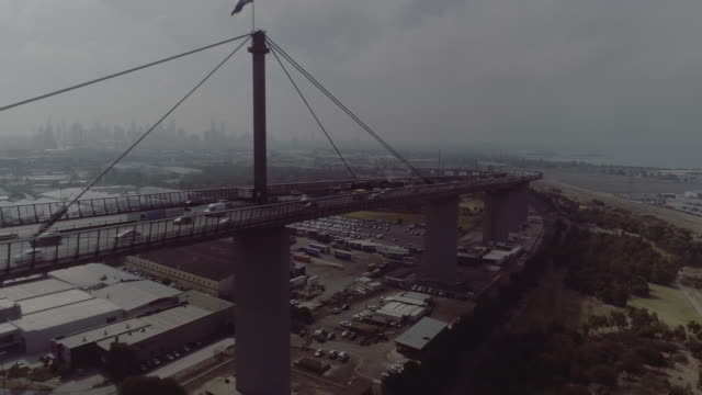 dynamic aerial view of melbourne's west gate bridge with australian flag. melbourne australia - cable box stock videos & royalty-free footage