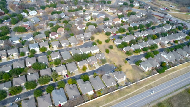 dynamic pan down across massive suburb neighborhood with modern layout pattern round rock , texas , aerial drone view - modern rock stock videos & royalty-free footage