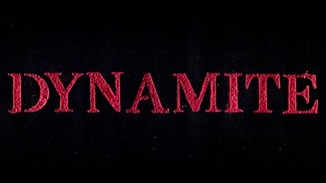 Dynamite written in red powder exploding in slow motion.