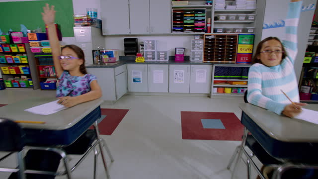 eager elementary students raise their hands to answer a question in class. - 教室点の映像素材/bロール