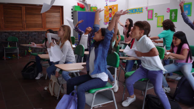 eager kids looking at the clock doing a countdown celebrating the end of term throwing papers to the air - finishing stock videos & royalty-free footage
