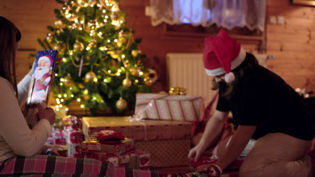 4K Eager sisters opening Christmas gifts near Christmas tree, real time
