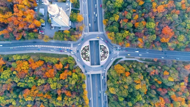 eagle eye aerial view shot over a busy city traffic circle, roundabout or crossroad - roundabout stock videos and b-roll footage