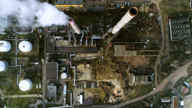 vidéos et rushes de tir de drone eagle eye regardant vers le bas de la vue aérienne sur un charbon alimenté usine - fumer du tabac