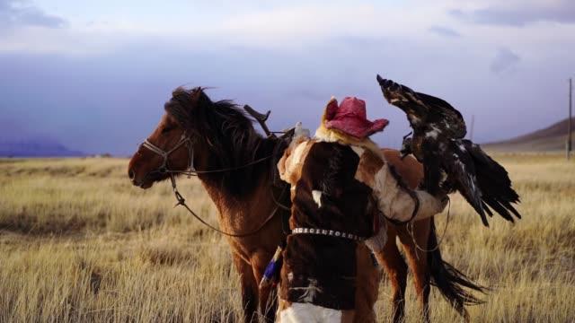 モンゴルの砂漠で馬に乗ったイーグルハンター - 遊牧民族点の映像素材/bロール