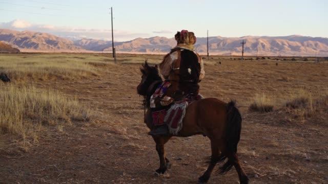 vidéos et rushes de chasseur d'aigle sur le cheval dans le désert en mongolie - mongolie indépendante